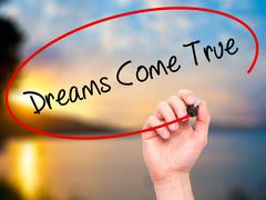 Man Hand writing Dreams Come True with black marker on visual screen. - stock illustration