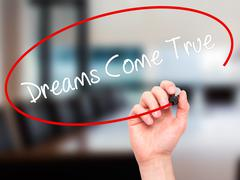 Stock Illustration of Man Hand writing Dreams Come True with black marker on visual screen.
