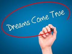 Man Hand writing Dreams Come True with black marker on visual screen. Stock Illustration