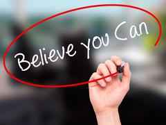 Man Hand writing Believe you Can with black marker on visual screen. - stock illustration