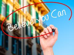 Man Hand writing Believe you Can with black marker on visual screen. Stock Illustration