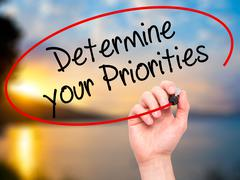 Man Hand writing Determine your Priorities with black marker on visual screen. - stock illustration