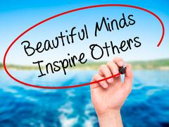 Stock Illustration of Man Hand writing Beautiful Minds Inspire Others with marker on visual screen.
