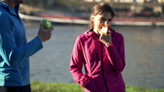 Young couple eating apple on the boardwalk in the city low angle - stock footage