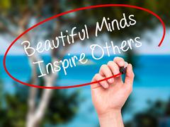 Man Hand writing Beautiful Minds Inspire Others with marker on visual screen. - stock illustration