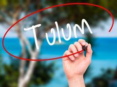 Man Hand writing Tulum with black marker on visual screen. - stock illustration