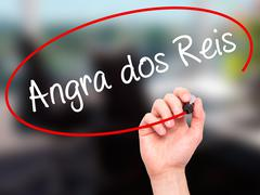 Man Hand writing Angra dos Reis with black marker on visual screen - stock illustration