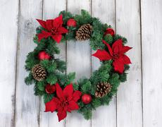 Holiday Poinsettia Christmas wreath on rustic white wooden boards Stock Photos