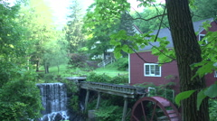 A red building with a water wheel and waterfall Stock Footage