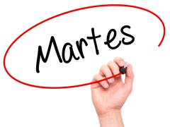 Man Hand writing Martes (Tuesday in Spanish) with black marker on visual screen. - stock illustration