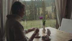 Pretty young lonely woman sitting in the cafe or home with a cup of coffee. Stock Footage