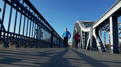 Stock Video Footage of Young couple jogging on the bridge low angle front, super slow motion