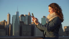 A beautiful woman taking selfies, NYC skyline in background - stock footage
