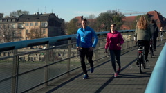 Stock Video Footage of Active couple jogging on the bridge in the city, super slow motion