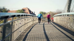 Two people jogging on the bridge in the city Stock Footage