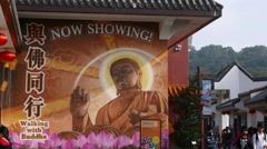 Pan from Buddha image on building wall to Big Budda statue far away on hill top Stock Footage