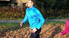 Couple jogging in autumn park, super slow motion Stock Footage