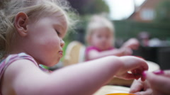 4K Mother feeding toddler twins in high chairs in the backyard Stock Footage