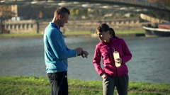 Male jogger with smartwatch and sportive woman talking close in the city river Stock Footage
