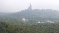 Large Buddha sculpture on hill top far away, foggy mountain landscape Stock Footage