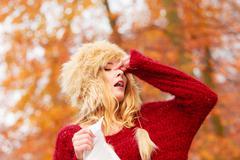 Sick woman in autumn park sneezing into tissue. Stock Photos