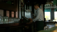 Bartender using cash register and tidying up the counter Stock Footage