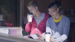 Man Reads Local Newspaper While His Boyfriend Uses Smart Phone Stock Footage