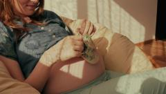 Small shoes for the unborn baby on the belly of pregnant women Stock Footage