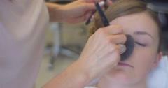 Stock Video Footage of Stylist is Putting a Powder to The Nose Making a Makeup For a Woman Model With