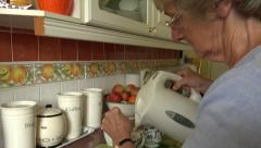 Senior woman boils kettle and pours water for tea - stock footage