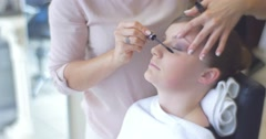 Stock Video Footage of Stylist is Putting a Mascara to the Lash Making a Makeup For a Woman Model With