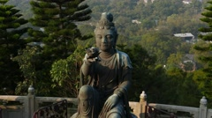 Small statue on the basement of Big Buddha monument, offering lotus flower Stock Footage
