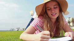 Pretty young student lying on the grass studying Stock Footage