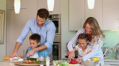 Attentive parents and their children cooking together - stock footage