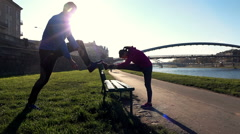 Young joggers couple stretching legs on the bench in the city, super slow motion Stock Footage