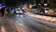 Young people helps push cars up hill in snow storm Stock Footage