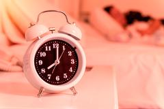 Alarm clock on the bed in bedroom, retro style Stock Photos