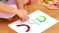 Girl painting abc onto some paper - stock footage