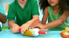 Kids playing together with modelling clay on a table Stock Footage