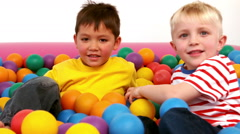 Two boys playing in a ball pit Stock Footage