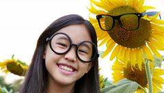 Happy Asian glasses girl with glasses sunflower in the field, Tilt up shot Stock Footage