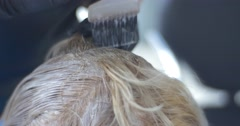 Stylist Makes Hair Coloring Blonding Close View Hairdresser's Hands In Black - stock footage