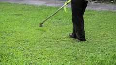 Worker with protective clothing cutting grass with grass cutter machine Stock Footage