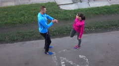 Young, sportive couple talking and stretching in the city Stock Footage