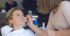 Stock Video Footage of Woman Stylist Beautician is Applying an Eyes Makeup For a Model Young Woman is