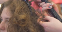 Curly Hairs Close Up Stylist is Creating Hairstyle Using The Iron Straightening Stock Footage