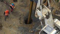 Workers with hydraulic hammer drilling machine at construction site Stock Footage