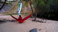 Woman sitting in hammock looking at waterfall. Stock Footage