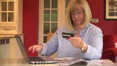 Senior woman buys from catalogue at home with credit card over the Internet - stock footage