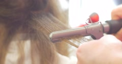 Stock Video Footage of Strand Close Up Steam Stylist Hairdresser Making Hairstyle by Corrugated Iron